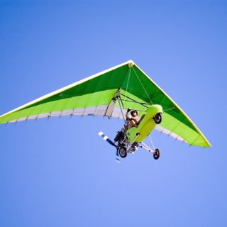 Airborne Motorized Ultralight Glider in a cloudless blue sky